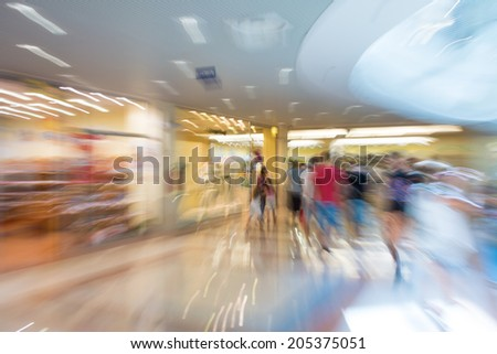 People silhouettes at shopping mall in motion blur - stock photo