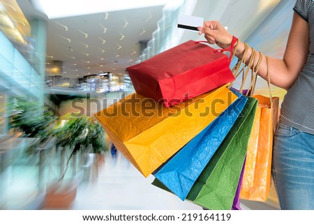 People silhouettes at shopping mall in motion blur. Intentional zoom effect - stock photo