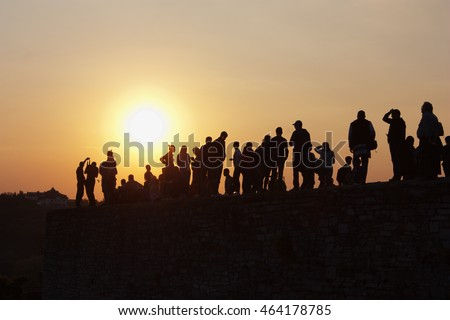 people silhouettes at sunset, watching the sunset