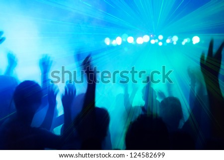 People silhouettes dancing to the disco beat. - stock photo