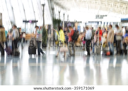 People silhouettes in motion blur, airport interior - stock photo