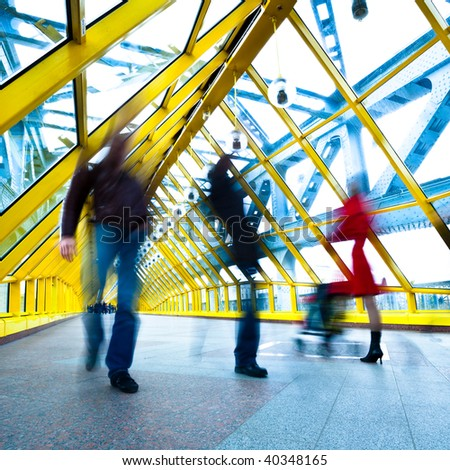 People silhouettes in motion in yellow passage, square composition - stock photo