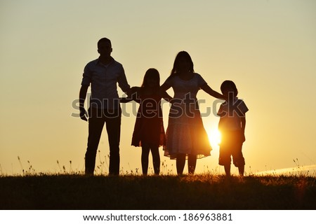 People silhouettes on summer sunset meadow - stock photo