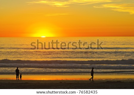 People Silhouettes on Sunset Californian Beach (Pacific Ocean, USA) - stock photo