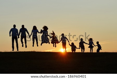 People silhouettes on sunset meadow having fun