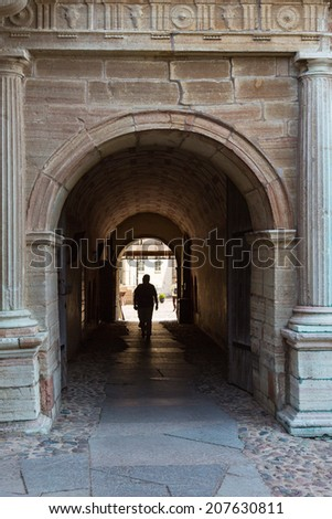 People silhouettes walking in an archway at a castle - stock photo