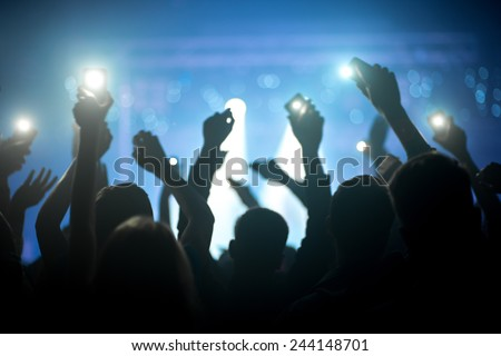 People silhouettes with raised hands holding phones with flashlights enjoying a concert at nightclub - stock photo