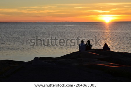 People sits by the shore and looks at the setting sun by the sea - stock photo