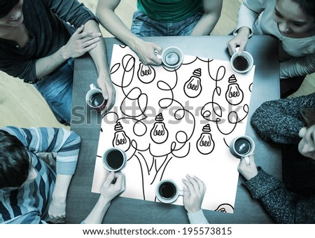 People sitting around table drinking coffee with page showing idea tree
