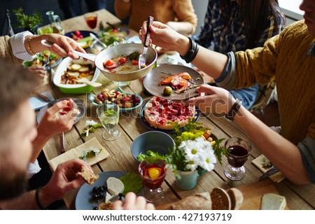 People sitting at dining table and eating - stock photo