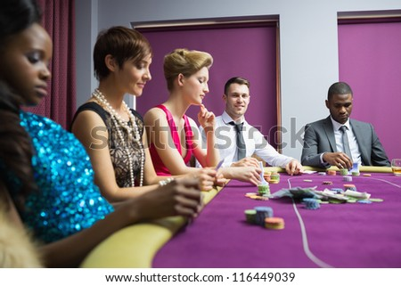 People sitting at poker table in casino - stock photo