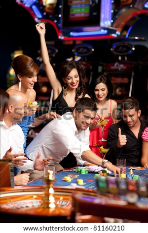 people sitting at the roulette table, placing their bets - stock photo