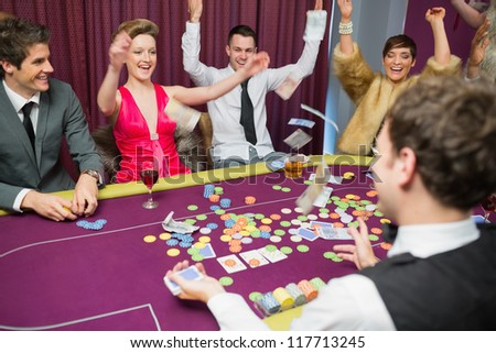 People sitting celebrating at poker game in casino - stock photo