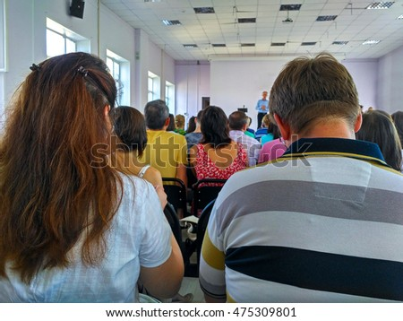 people sitting in a conference hall listening the presentation