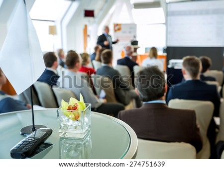 People sitting in the background on the negotiations at conference room. In foreground is a table with a flag and a mobile phone - stock photo