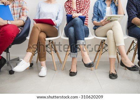 People sitting in the raw at the passage - stock photo