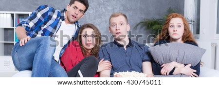 People sitting on couch with afraid faces