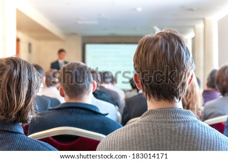 people sitting rear at the business conference and the speaker at the screen - stock photo