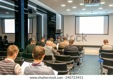 people sitting rear at the business conference and the white screen with a place for your text - stock photo