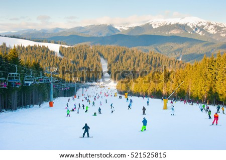 People skiing and snowboarding on a ski slope