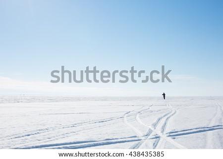 People skiing on the frozen lake. - stock photo