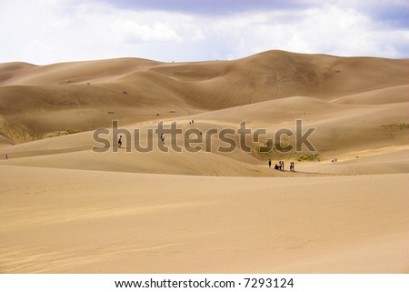 People small like ants walking far-away in dunes with sand being blown over by wind