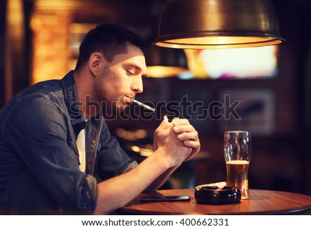 people, smoking and bad habits concept - man drinking beer and lighting cigarette at bar or pub - stock photo