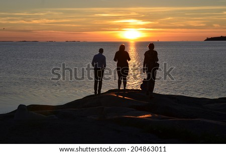 People standing by the shore and looks at the setting sun by the sea - stock photo