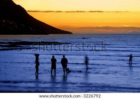 People standing in the ocean after sunset in Gordon's Bay, South Africa. Slow shutter speed results in some movement on people and the effect of foaming water. - stock photo