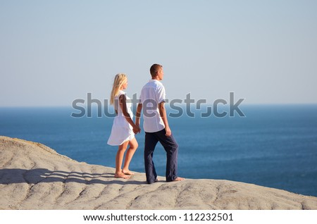 People standing on a mountain and looking at the sea holding hands - stock photo