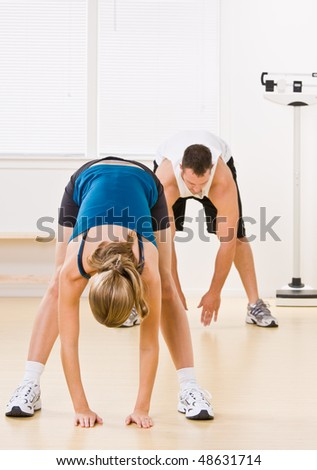 People stretching in health club