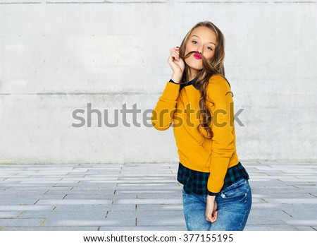 people, style and fashion concept - happy young woman or teen girl in casual clothes having fun making mustache of her hair strand over urban street background - stock photo