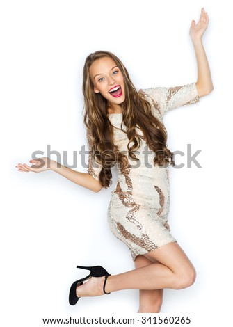 people, style, holidays, hairstyle and fashion concept - happy young woman or teen girl in fancy dress with sequins and long wavy hair having fun - stock photo