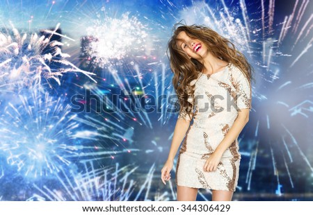 people, style, holidays, hairstyle and fashion concept - happy young woman or teen girl in fancy dress with sequins and long wavy hair dancing at party over firework at night city background - stock photo