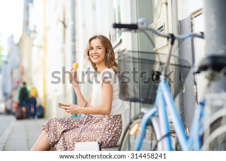 people, style, technology, leisure and lifestyle - happy young hipster woman with smartphone and fixed gear bike eating ice cream on city street - stock photo