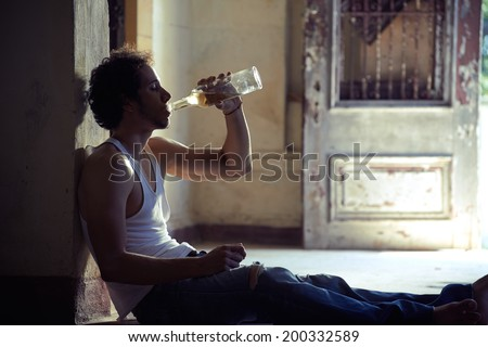 People, substance abuse and domestic violence. Portrait of young alcoholist drunk male drinking whisky at home - stock photo