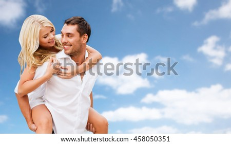 people, summer holidays, vacation and love concept - happy couple having fun over blue sky and clouds background