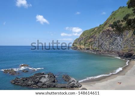 People sunbathing at the beach of an island - stock photo