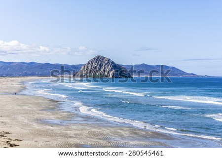 People sunbathing near Majestic Morro Rock over looking the Pacific Ocean, next to Morro Strand state beach, on the California Central Coast, near Cambria, CA. - stock photo