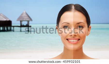 people, suntan, travel and summer holidays concept - close up of beautiful smiling woman with half face tanned over exotic tropical beach with bungalow background - stock photo