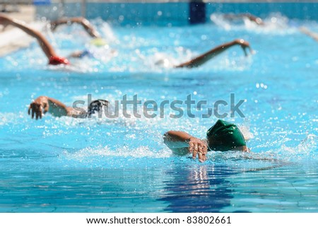 People swimming in a open air pool
