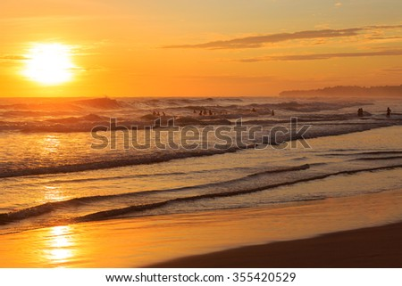 People swimming in the ocean at sunset - stock photo