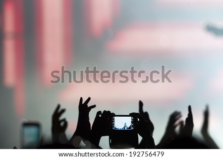 People taking photographs with touch smart phone during a music entertainment public concert  - stock photo