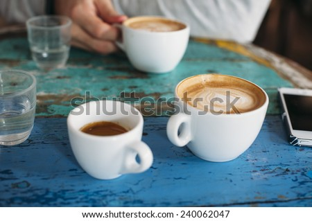 People talking in the cafe while having some fresh coffee (two cappuccinos and one espresso with beautiful tiger crema)