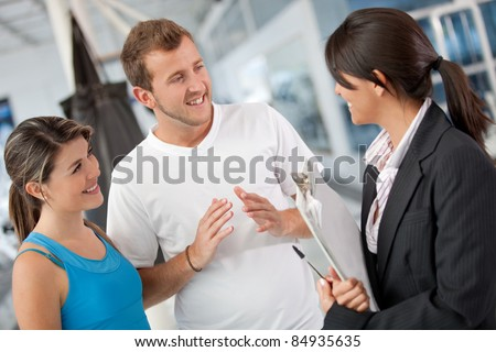 People talking with the gym manager and looking at the facilities - stock photo