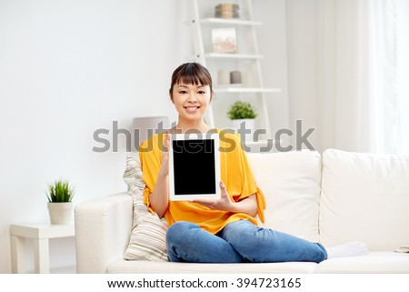 people, technology, advertisement and leisure concept - happy young asian woman sitting on sofa and showing tablet pc computer blank black screen at home