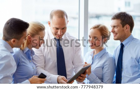 people, technology and corporate concept - business team with tablet pc computer at office