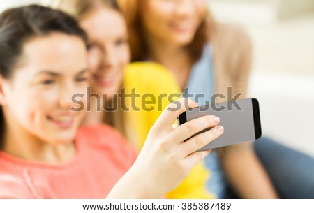 people, technology and leisure concept - close up of young women or teenage friends taking selfie with smartphones at home - stock photo