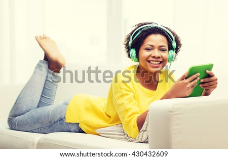 people, technology and leisure concept - happy african american young woman lying on sofa with tablet pc computer and headphones listening to music at home