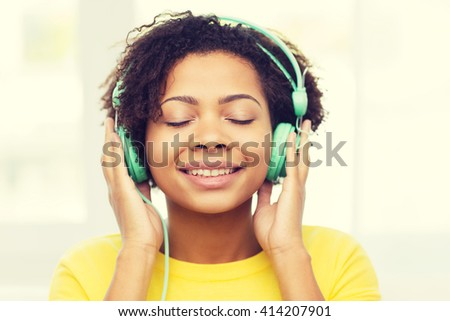 people, technology and leisure concept - happy african american young woman sitting on sofa with headphones listening to music at home - stock photo